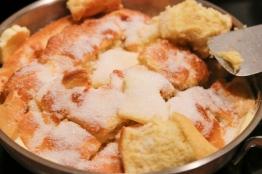 Den Schmarren zerreißen und mit Butter und Zucker karamellisieren